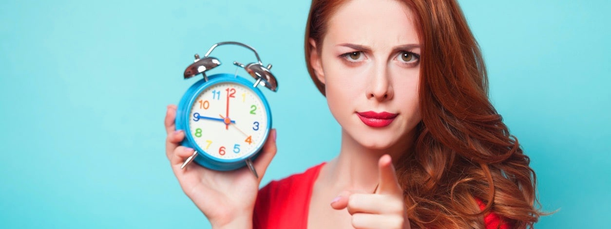 Girl with alarm clock on blue background.