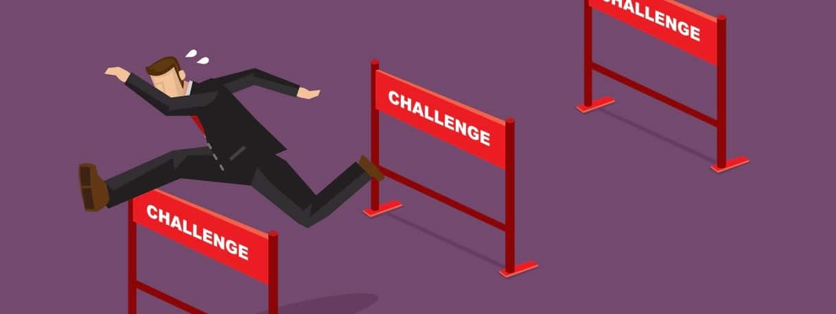 Businessman jumping over series of hurdles with text Challenge on them.